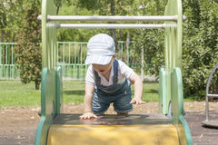 Baby, das zur Spitze des Schiebers am Spielplatz erreicht Hartnäckigkeit c Lizenzfreies Stockfoto