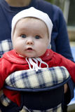 Baby daughter in baby carrier outdoors Royalty Free Stock Images