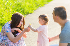 Baby daughter Giving Mother Flowers in the park.  Stock Images