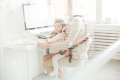 Daughter of accountant. Baby daughter of young accountant sitting in front carrier close to her mother during work in office stock images