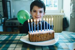 Child in the day of his ninth birthday blowing the candles on th. Baby in the day of his ninth birthday blowing the candles on the cake, in the kitchen of his Royalty Free Stock Photo