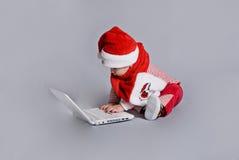 Baby de Kerstman met witte laptop stock afbeelding