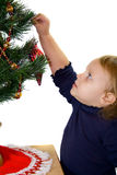 Baby decorating Christmas tree. Stock Image