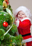 Baby decorating Christmas tree Stock Images