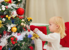 Baby decorating Christmas tree Royalty Free Stock Images