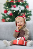 Baby in deer suit with Christmas present box Royalty Free Stock Images
