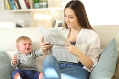 Baby demanding attention and mother ignoring him. Baby crying demanding attention and his mother ignoring him sitting on a couch in the living room at home Stock Images
