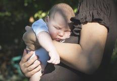 Baby in den Armen seiner Mutter Stockfotos