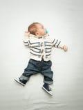Baby in den Jeans, die das soother liegt auf Bett halten Lizenzfreies Stockbild