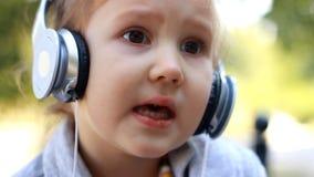 Baby in den Kopfhörern hörend Musik und ein Lied singend Porträtnahaufnahme stock video footage
