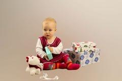 Baby in den roten Kleidersitzen-und -öffnungs-Geschenkboxen Stockfotos
