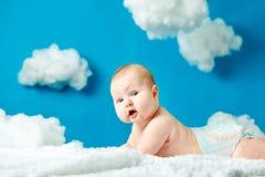 Baby in den Windeln, die auf einer Wolke im Himmel liegen stockfotografie