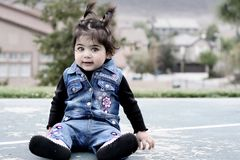 Baby in denim. A baby girl dressed in denim is sitting on a basketball ground Stock Images