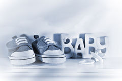 Baby denin shoes. Little baby denim running shoes with pacifier on shelf Stock Photos