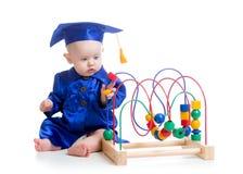 Baby in der Akademikerkleidung mit pädagogischem Spielzeug Lizenzfreie Stockfotografie