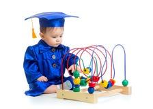 Baby in der Akademikerkleidung mit pädagogischem Spielzeug Lizenzfreies Stockfoto