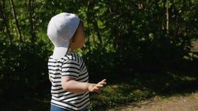 Baby in der Kappe und in T-Shirt, die entlang auf der Straße laufen stock footage