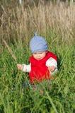 Baby in der roten Weste, die draußen auf Gras sitzt Stockbild