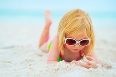 Baby in der Sonnenbrille, die auf Strand legt Stockbild