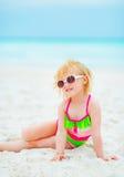 Baby in der Sonnenbrille, die auf Strand sitzt Lizenzfreie Stockbilder
