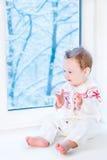 Baby in der Strickjacke mit Schneeflocke nahe bei Fenster Stockfotos