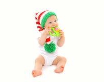 Baby in der Strickmütze, die mit Spielzeug auf Weiß spielt Lizenzfreies Stockbild