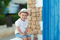 Baby des kleinen Jungen im Hut, der im Haus im Sommer und im smilin sitzt Stockbilder