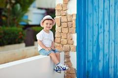 Baby des kleinen Jungen im Hut, der im Haus im Sommer und im smilin sitzt Lizenzfreie Stockfotos