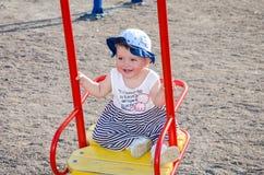 Baby des kleinen Mädchens in einer Kappe spielt mit Spielwaren in einem Sandkasten mit Sand auf dem Spielplatz Stockbilder