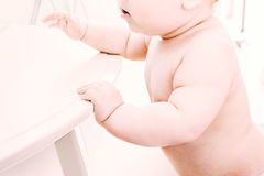The baby develops, the boy learns to walk. The baby clings to the edge of the table Stock Photo