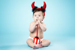 Baby with devil horns on blue background Royalty Free Stock Photography