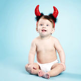 Baby with devil horns on blue background Stock Photography