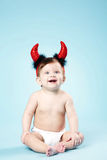 Baby with devil horns on blue background Royalty Free Stock Image