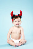 Baby with devil horns on blue background Royalty Free Stock Photo