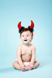 Baby with devil horns on blue background Royalty Free Stock Images