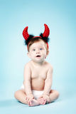 Baby with devil horns on blue background Stock Images