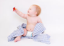 Baby in a diaper and a plaid shirt with a pacifier in her raised. Baby in a diaper and a plaid shirt sitting on the floor with a pacifier in a raised hand royalty free stock photography