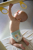Baby in a diaper in playpen.  Royalty Free Stock Photography