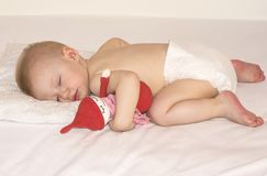 Sleeping baby in a diaper with a handmade toy. Baby in a diaper is sleeping on a white blanket with a handmade toy Royalty Free Stock Image