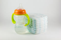 Baby diapers and bottle on a white background Royalty Free Stock Image