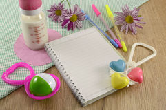 Baby diary with colorful playthings. Baby diary still life with colorful playthings and milk bottle Royalty Free Stock Photos