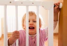 Baby dichtbij veiligheidspoort Stock Afbeeldingen