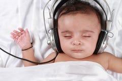 Baby die aan muziek met hoofdtelefoons luistert Royalty-vrije Stock Afbeeldingen