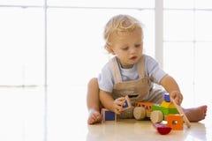 Baby die binnen met stuk speelgoed vrachtwagen speelt Stock Foto's