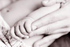Baby die de hand van een volwassene, in zwart-wit grijpen stock afbeelding