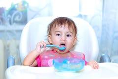 Baby die in de keuken op het sittting eten Royalty-vrije Stock Foto's