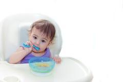 Baby die in de keuken op het sittting op de lijst eten Stock Foto's
