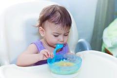 Baby die in de keuken op het sittting op de lijst eten Stock Fotografie