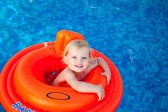 Baby die in de oranje vlotter zwemmen stock fotografie