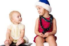Baby die de sibling zuster in de hoed van de Kerstman bekijkt Stock Afbeelding